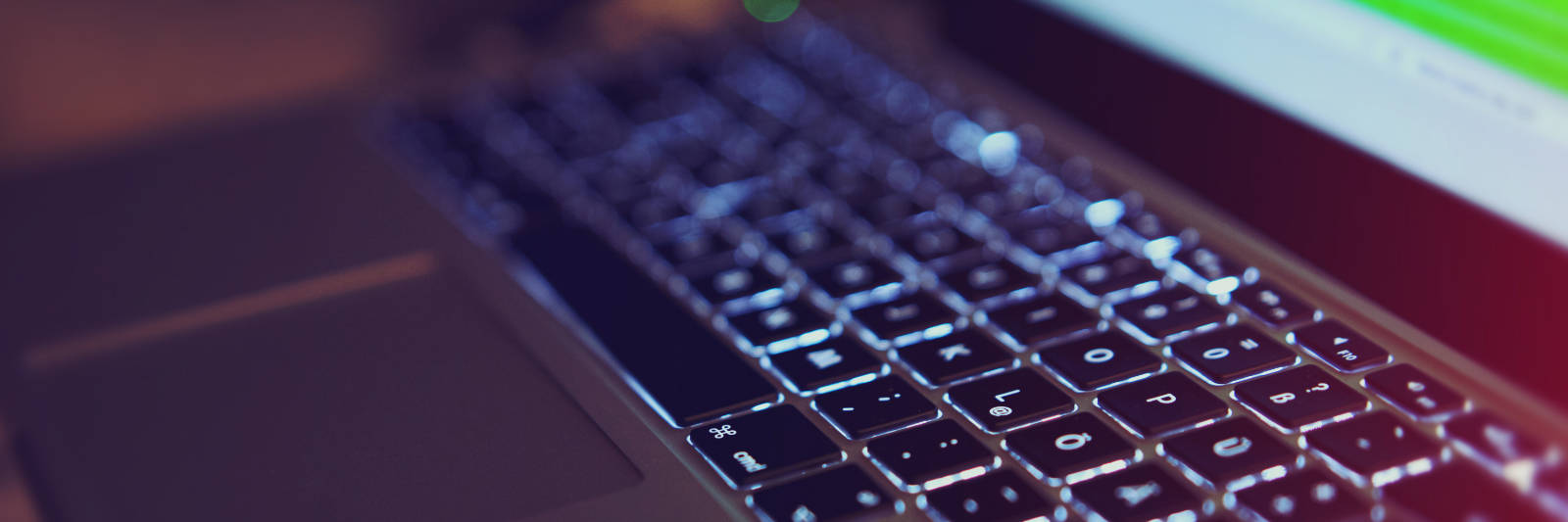 Image of a MacBook Pro with backlit keyboard in the dark